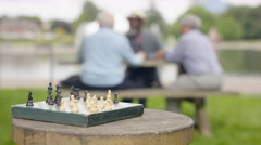 4K Focus on chess board outdoors in the park, happy senior friends in background Stock Footage