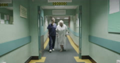 An attractive female medical assistant or nurse helps an elderly lady Stock Footage