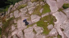 Aerial high shot of man above a tall cliff and a mountain forest Stock Footage