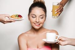 Hands offering cake and drinks to young beautiful naked girl Stock Photos