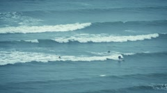 Surfers Catching Waves Out At Sea Stock Footage