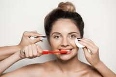 Hands careing skin while young beautiful naked girl cleaning teeth Stock Photos