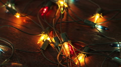 Flashing garland lying on the wooden floor. Christmas background Stock Footage