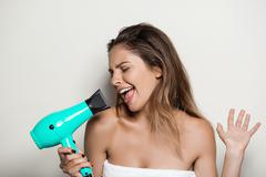 Young beautiful naked girl in towel singing with hairdryer Stock Photos