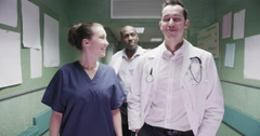 Two young doctors and a young nurse enjoy some light hearted chat Stock Footage