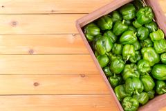 Crate of fresh green peppers from top view Stock Photos