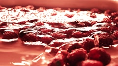 Red raspberries rolling in shallow water, super slow motion video Stock Footage
