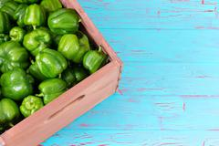 Corner of crate fully stocked with green peppers - stock photo
