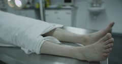 Dead male body laid out on an autopsy table at night. Stock Footage