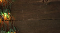 Flashing garland on the wooden floor. Christmas background Stock Footage
