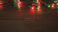 flashing garland on the wooden floor. Christmas background - stock footage