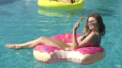 Girls sitting outdoors eating ice creams next to pool on a summer day in a Stock Footage