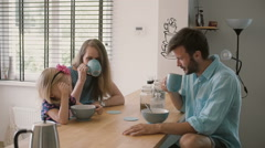 Young happy family is having peaceful breakfast in the morning. Slow motion Stock Footage