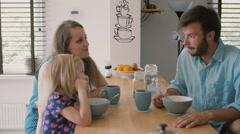 Young father is looking at his wife and daughter at the kitchen table during Stock Footage