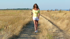 Slow motion.  Beautiful  sexual woman   go  on  dirt road. Slider shot Stock Footage