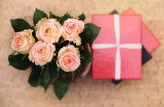 Vase with roses and gift with ribbon Stock Photos