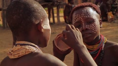 Two People From A Tribe in The Omo Valley Doing Traditional Dot Face Painting Stock Footage