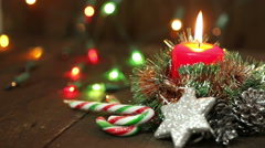 One burning candle and Christmas decorations. Background Stock Footage