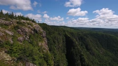 Aerial shot of a cliff and deep gorge and a mountain forest Stock Footage