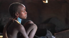 Young Girl From A Tribe WIthin The Omo Valley Sitting in Profile Stock Footage
