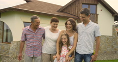 Happy family in three generations with children in summer in front of a house Stock Footage