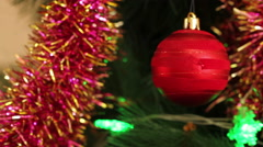 Red ball on the Christmas tree with blinking garlands in tinsel. Stock Footage