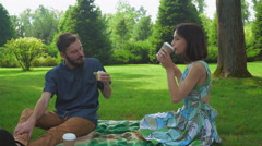 The guy with the girl eat salad sandwiches on picnic washed down with coffee Stock Footage