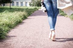 girl in jeans walking along the path of the camera, rear view, high heel shoes - stock photo