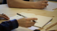 Close-up view of people writing and drawing important information - stock footage