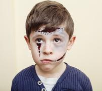 Little cute boy with facepaint like zombie apocalypse at halloween party close Stock Photos