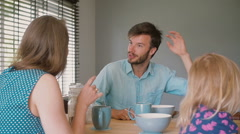 A young dark-haired father is having a conversation with his beautiful wife at Stock Footage