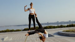 Two young woman doing callisthenics acrobatic show at morning city Stock Footage