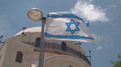 Israel flag waving in wind against blue sky Stock Footage
