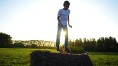 Child have fun jumping on the hay Stock Footage
