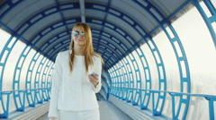 Stylish young woman walking along the glass tunnel. Keeps the phone in your hand Stock Footage