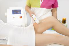 Beautiful woman getting permanent laser hair removal at beauty salon Stock Photos
