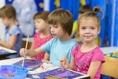 Cute kids doing their craft, painting at kindergarten Stock Photos
