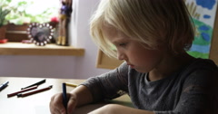 Closeup portrait of preschooler with blonde long hair who draws in the Stock Footage