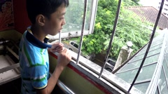 Pensive boy looking out through hospital window Stock Footage