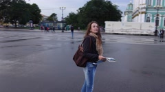 Tourist girl look around Palace Square, hold city map, wet asphalt after rain Stock Footage