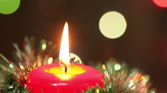 Burning Christmas candle. Flashing blurred background. Christmas decorations - stock footage