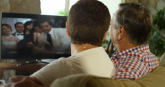 A happy senior couple watching television together, mature wife holding remote Stock Footage