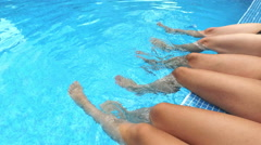 Girl's beauty legs in the pool making splashes Stock Footage
