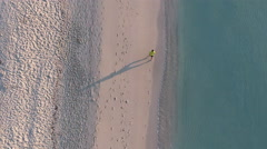 Overhead aerial drone shot of jogger in Miami Beach Stock Footage