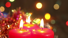 Three burning Christmas candles surrounded by garland flashing. Background Stock Footage