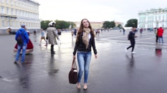 Amazed tourist girl look around on wet Palace Square, enjoy sights, orbital shot Stock Footage