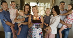 Multi generation family celebrating birthday at home, blowing out candles on Stock Footage