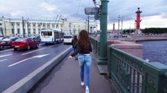 Tourist girl happily run on Palace Bridge with cuddle toy, slow motion chase Stock Footage
