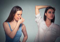 two women, one pinching nose something stinks, girls underarm - stock photo