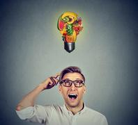 Eating healthy. Man looking up light bulb made of fruits - stock photo